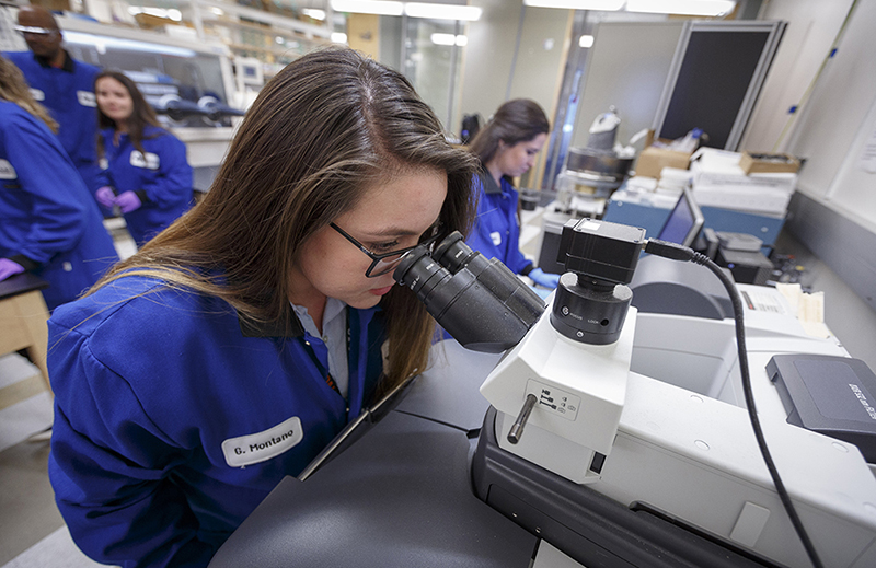 A student uses a research microscope during a materials science and engineering lab.